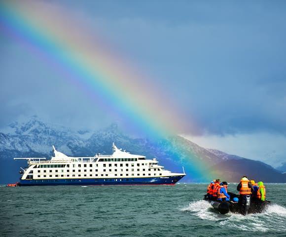 Stella Australis, Patagonian cruising vessel with Zodiac excursion vessel under rainbow, Patagonia
